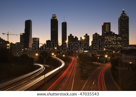 Cars on a freeway traveling through downtown at night. Horizontal shot.