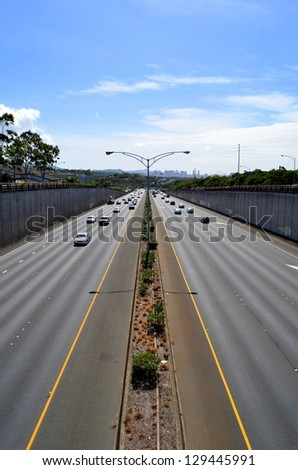 Cars On A Highway With Downtown In The Distance With Copy Space - stock photo