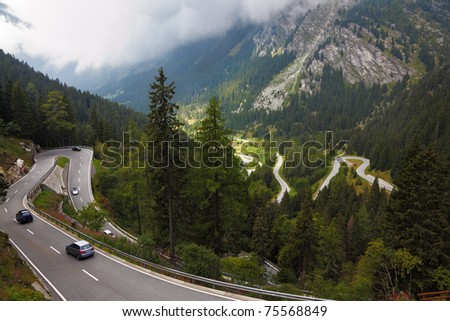 Cars on a steep mountain road turn in the Italian Alps - stock photo