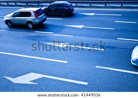 Cars on asphalt road with poits in blue - stock photo