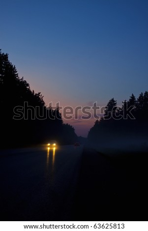 Cars on forest road at cold night. Very dark scene. - stock photo
