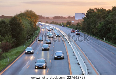 Cars on highway road at sunset - stock photo