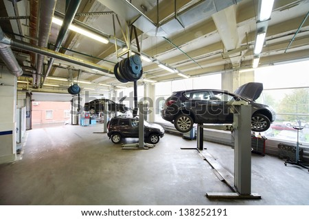 Cars on lifts in small service station. Cars prepared to diagnosis and repair. - stock photo