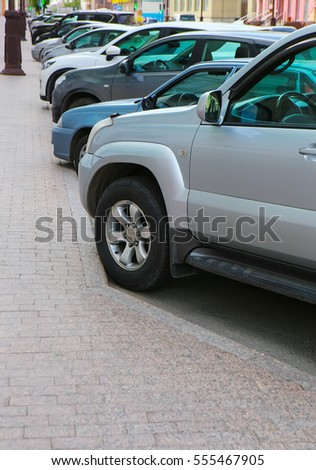 cars on parking near sidewalk in row in city