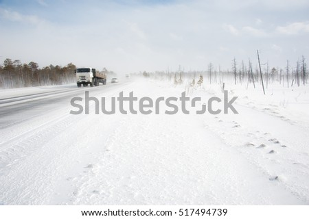 Cars on the winter road in snowstorm time. Risk of snow and ice. Blizzard.