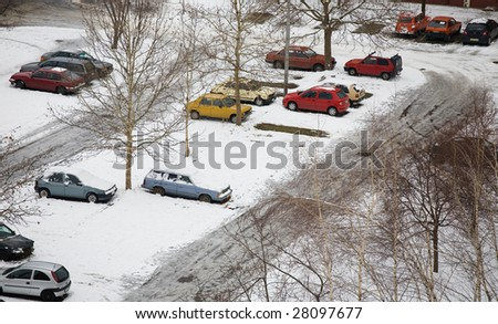 cars parked in parking lot with winter snow - stock photo