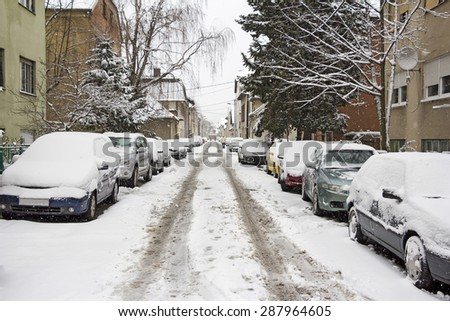 Cars parked on the street covered with fresh snow - stock photo