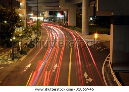 Cars racing under a highway in Tokyo, Japan - stock photo