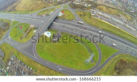 Cars ride by bridge of Abramtsevskaya overpass on Moscow beltway at autumn day. View from unmanned quadrocopter
