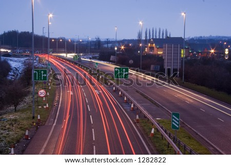 Cars slamming on their brakes as they approach road works and speed restrictions. Blurred over long shutter delay at dusk. - stock photo