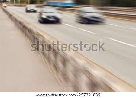 Cars speeding on highway lane; concept of speeding, transport safety and rush. Radial zoom effect defocusing filter applied, with vintage instagram look to stress speed and excitement. - stock photo