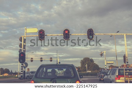 Cars waiting in front of traffic lights at sunset - stock photo