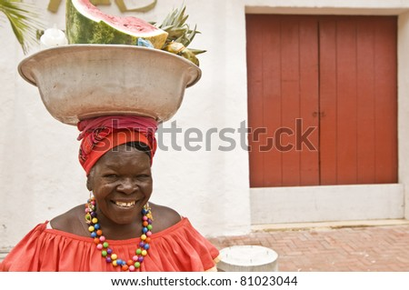 "CARTAGENA, COLOMBIA - JULY 30: ""Palenquera"" woman sells fruit on July 30, 2010 in Cartagena, Colombia. Palenqueras are a unique African descendant ethnic group found in the north of South America. - stock photo"