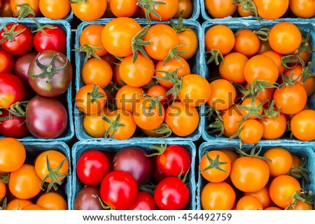 Cartons of fresh heirloom tomatoes at a market - stock photo