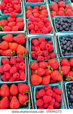 Cartons of fresh strawberries, blueberries and raspberries at a farmers market. - stock photo