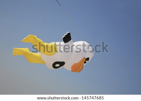 Cartoon duck shaped kite flying in a clear blue sky