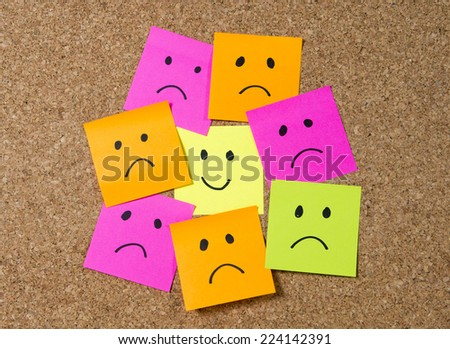 Cartoon face expression on note surrounded by sad and depressed faces on cork message board in happiness versus depression and smile against adversity concept - stock photo