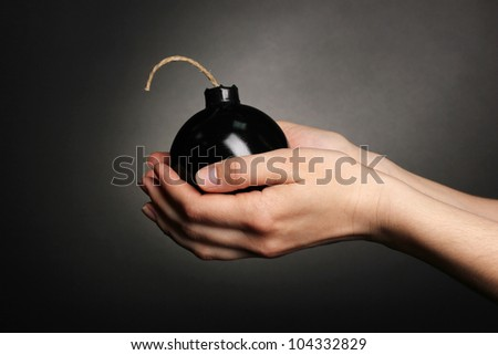 Cartoon style bomb in hands on black background - stock photo