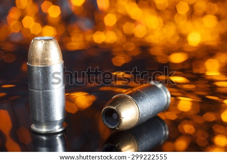 Cartridges for a handgun with hollow point bullets and an orange background - stock photo