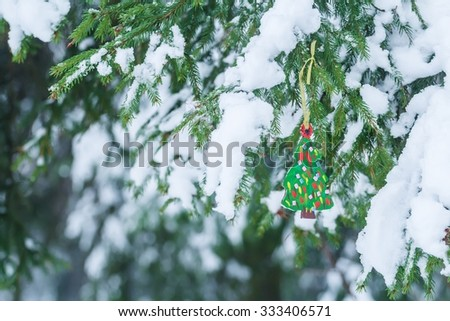Carved and painted wooden diy Christmas tree displaying on snowy spruce branch