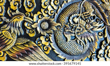 Carved Dragon Fighting with Swan on The Wooden Background Texture - stock photo