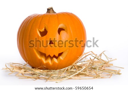 Carved face in pumpkin on a bed of straw - stock photo