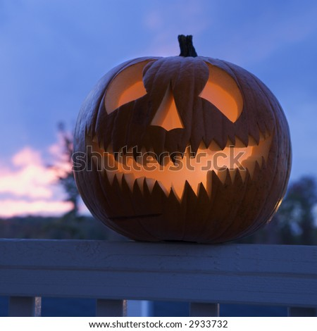 Carved Halloween pumpkin perched on porch railing. - stock photo