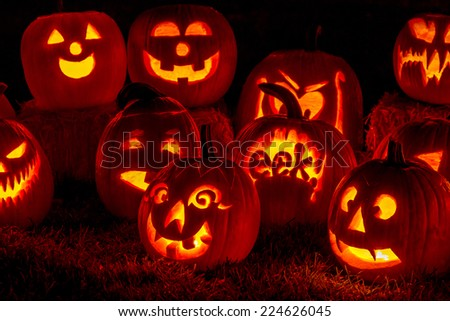 Carved Halloween pumpkins lit with candles sitting on fallen leaves and hay bales - stock photo