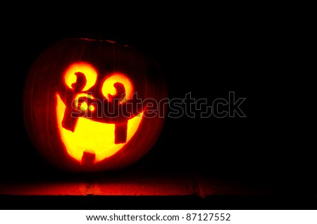 Carved happy jack-o-lantern on stoop at night.