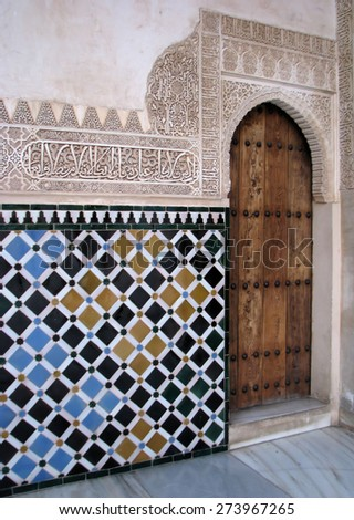 Carved islamic wall decoration filled with colourful tiles, Alhambra, Granada, Spain. - stock photo