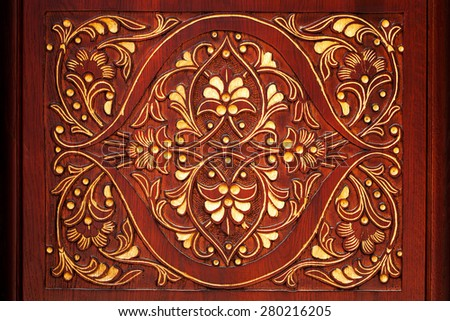 Carved pattern on a dark background with a floral theme - stock photo