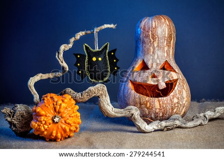 Carved pumpkin and black bat from felt on the branch at Halloween party  - stock photo