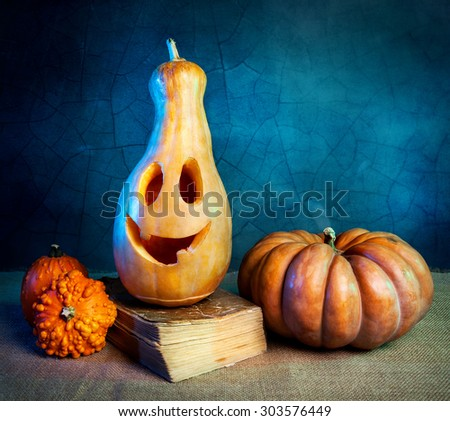 Carved pumpkin on the old book at Halloween party  - stock photo