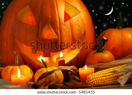 Carved pumpkin with candles and corn - stock photo