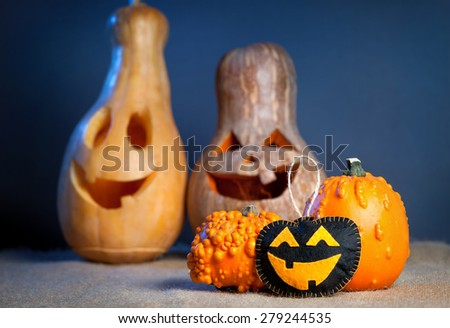 Carved pumpkins and handmade toy from felt on the sackcloth at Halloween party  - stock photo