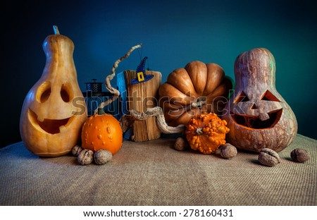 Carved pumpkins, old book, nuts and witch hat from felt on the branch at Halloween party  - stock photo