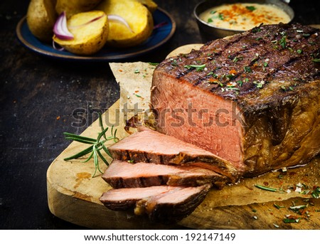 Carved rare roast beef seasoned with fresh rosemary, spices and herbs on an old wooden chopping board in a country kitchen - stock photo