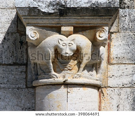 Carved stone capital of strange co-joined animals on the exterior wall of St. Antimo's Abbey or Abbazia di Sant'Antimo, Tuscany, Italy