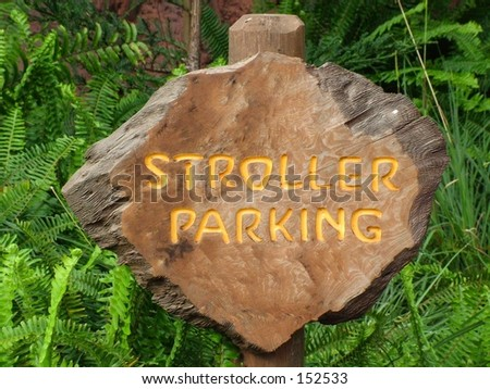 Carved wood stroller parking sign against green foliage - stock photo