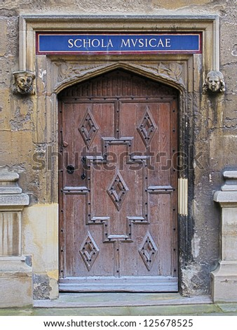 Carved wooden door at entrance to School of Music, Bodleian Library, Oxford, United Kingdom. - stock photo