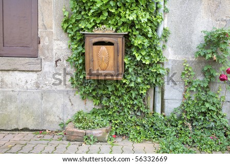 Carved wooden mailbox with Ivy growing on a stone wall. Dun-le-Palestel, La Creuse, Limousin, France. - stock photo