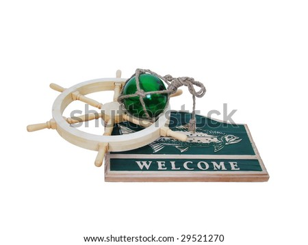 Carved wooden nautical sign with a large fish and the word welcome against green with a ship wheel and glass float - Path included - stock photo