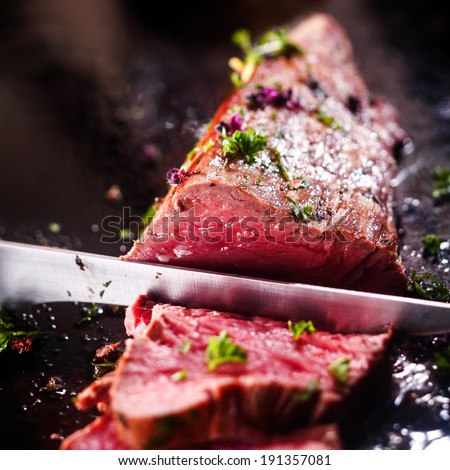 Carving a portion of delicious rare roast beef sirloin of fillet seasoned with fresh herbs with a large steel carving knife - stock photo