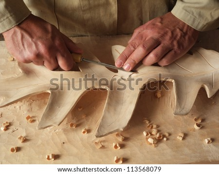 carving an oak leaf in wood - stock photo