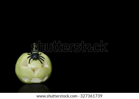 Carving Halloween Guava with a Spider on Black Background