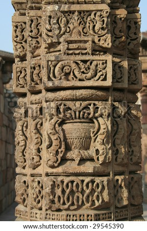 Carving of intricate design in stone pillar