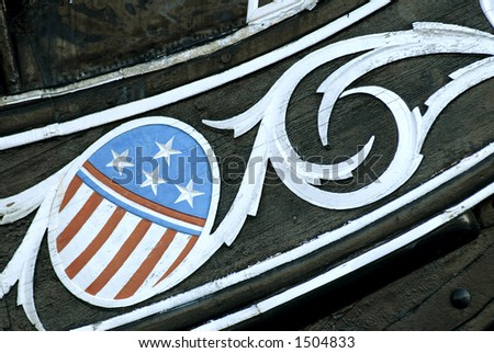 Carving of the stars and stripes on the bow of the USS Constitution in Boston Harbor - stock photo