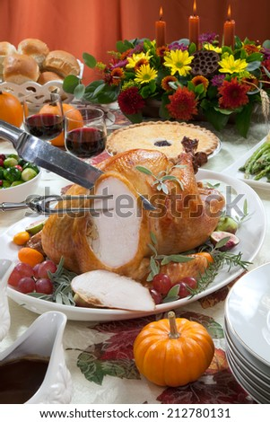 Carving roasted turkey on a server tray garnished with fresh figs, grape, kumquat, and herbs on fall harvest table. Red wine, side dishes, pie, and gravy. Decorated with mini pumpkins, candels.  - stock photo