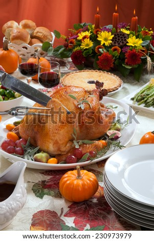 Carving roasted turkey on a server tray garnished with fresh figs, grape, kumquat, and herbs on fall harvest table. Red wine, side dishes, pie, and gravy.  - stock photo
