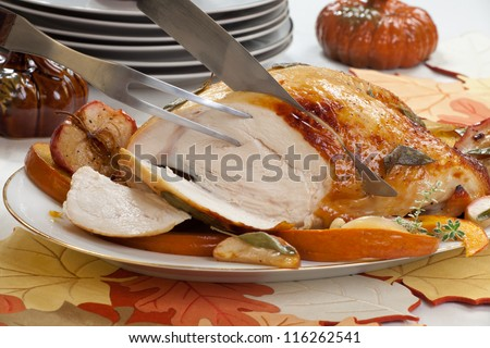 Carving sage - honey butter rub turkey breast garnished with roasted pumpkin and apples in fall themed surrounding. - stock photo